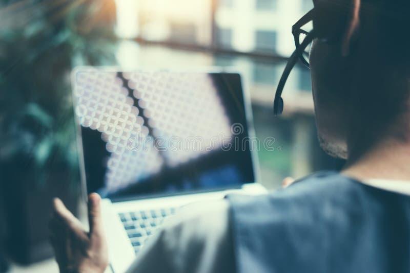 Zamyka w górę widoku jest ubranym audio słuchawki i robi wideo rozmowie przez cyfrowej pastylki mężczyzna Coworker pracuje na jeg obraz royalty free