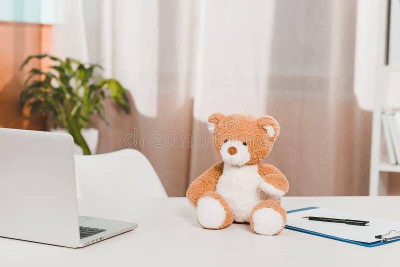 zamyka w górę widoku laptop, miś i notepad, przy lekarki miejscem pracy obraz royalty free