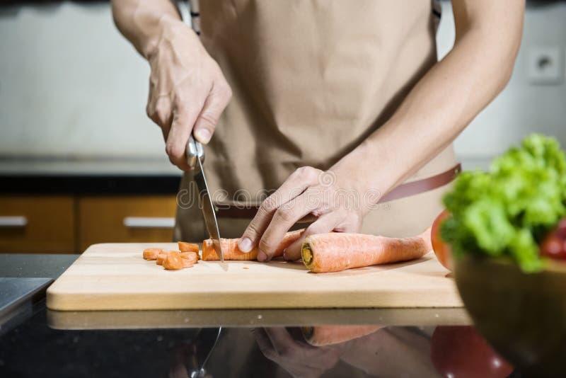 Zamyka w górę widoku mężczyzna ręki przecinania marchewka na tnącej desce obraz stock