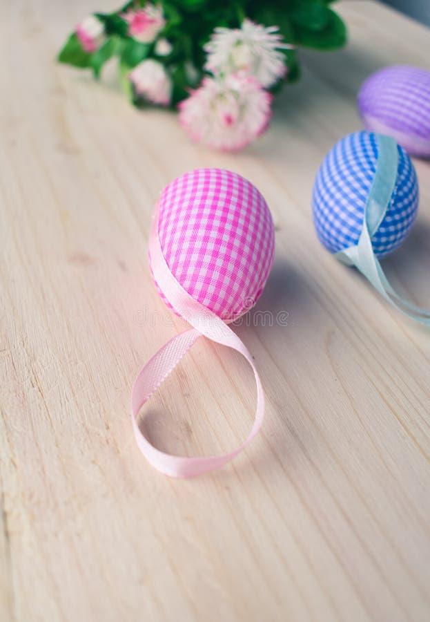 Zamyka w górę widoku menchie i błękitne w kratkę Wielkanocne jajko stokrotki na bladym drewnianym tle dekoracji, białych i różowy obrazy stock