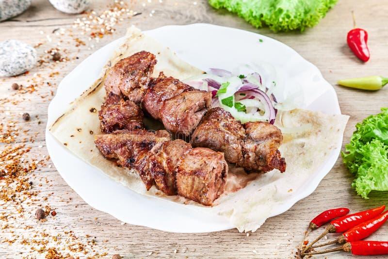 Zamyka w górę widoku na słuzyć gotujący na grill wieprzowinie szaszłyka lub grilla mięso na pita Shish kebab, tradycyjna georgian obraz stock