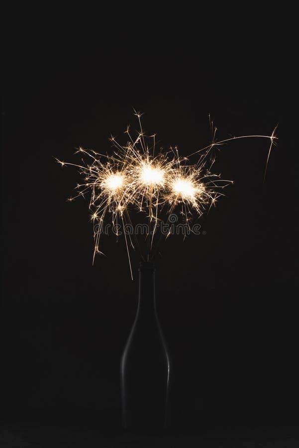 zamyka w górę widoku płonący sparklers w butelce odizolowywającej na czerni obrazy royalty free