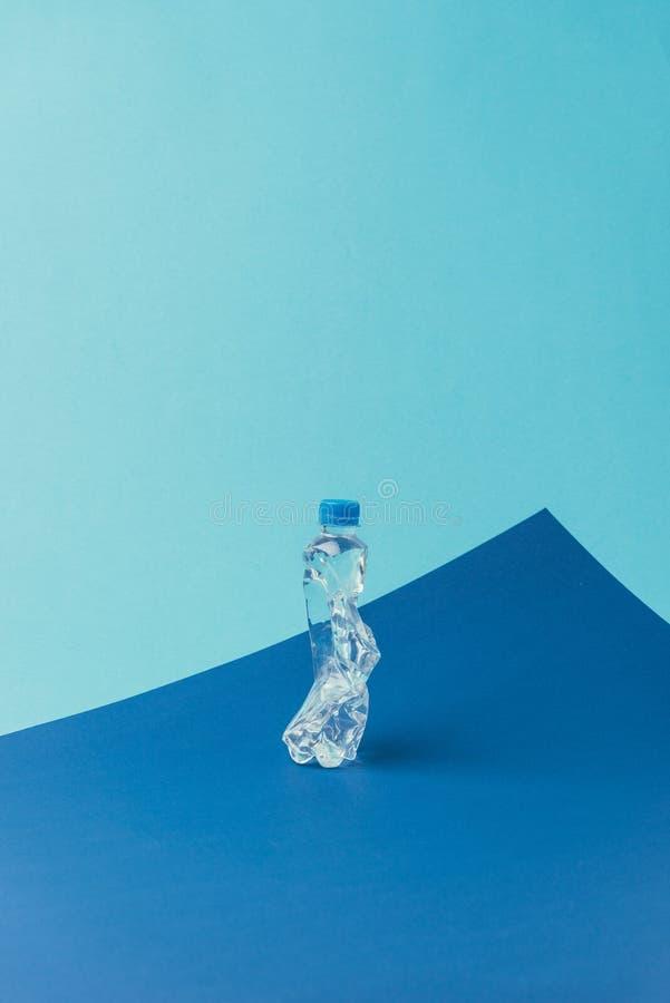 zamyka w górę widoku plastikowa butelka na błękitnym tle, przetwarza pojęcie, zdjęcie royalty free
