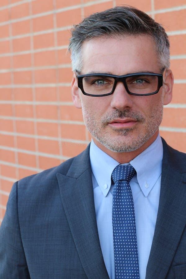 Zamyka w górę wieka średniego mężczyzna Jest ubranym garnitur i Eyeglasses ono Uśmiecha się przy kamerą, Odizolowywającą na ścian zdjęcie stock