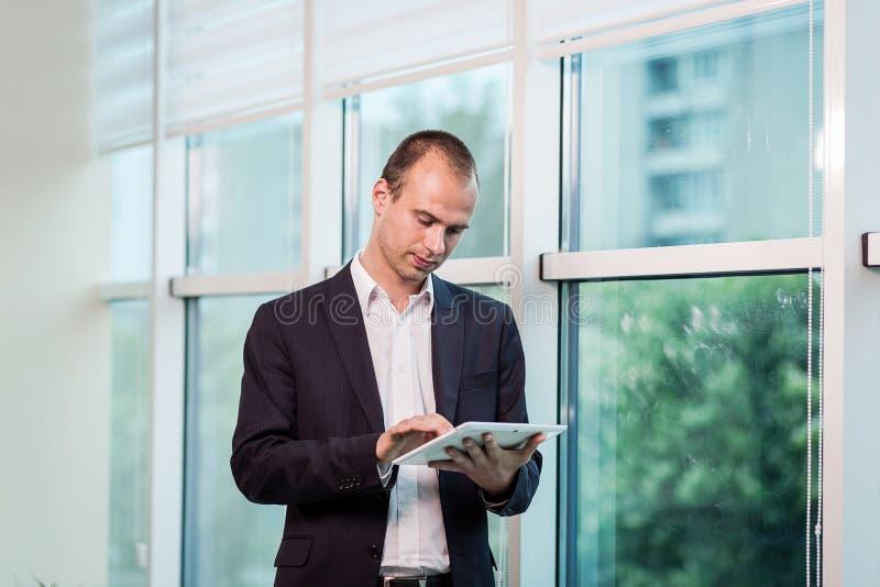 Zamyka w górę wizerunku trzyma cyfrową pastylkę biznesowy mężczyzna, portret fotografia stock
