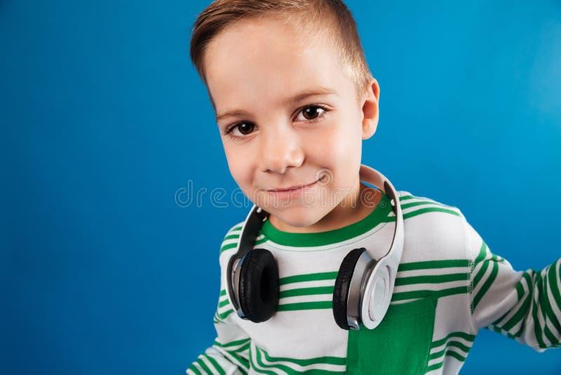 Zamyka w górę wizerunku uśmiechnięta młoda chłopiec pozuje z hełmofonem zdjęcie stock