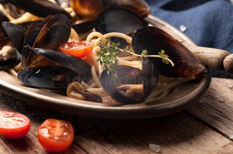 Zamyka w górę złotego talerza z włoskim makaronem, mussels, rżnięci pomidory i rozmaryny, zdjęcia royalty free