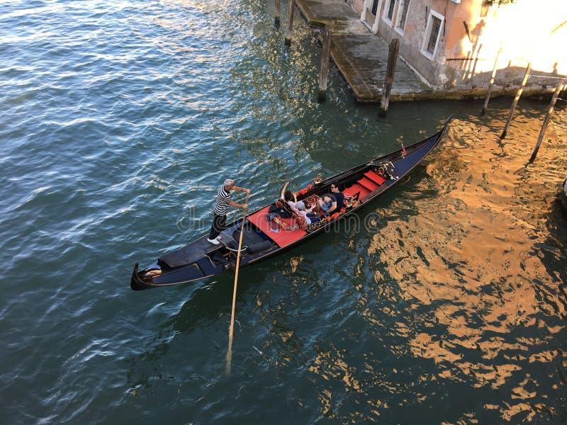 zamyka w górę zasięrzutnego widoku gondolier paddling jego gondolę z parą turyści wzdłuż wod kanał w Wenecja, Włochy obraz stock