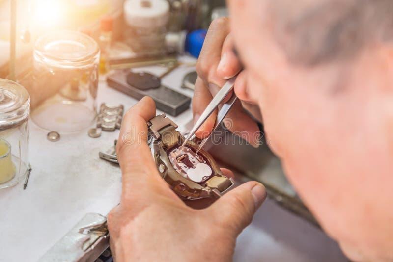 Zamyka w górę zegarmistrza naprawiania mechanizmu starego zegarka zdjęcie royalty free