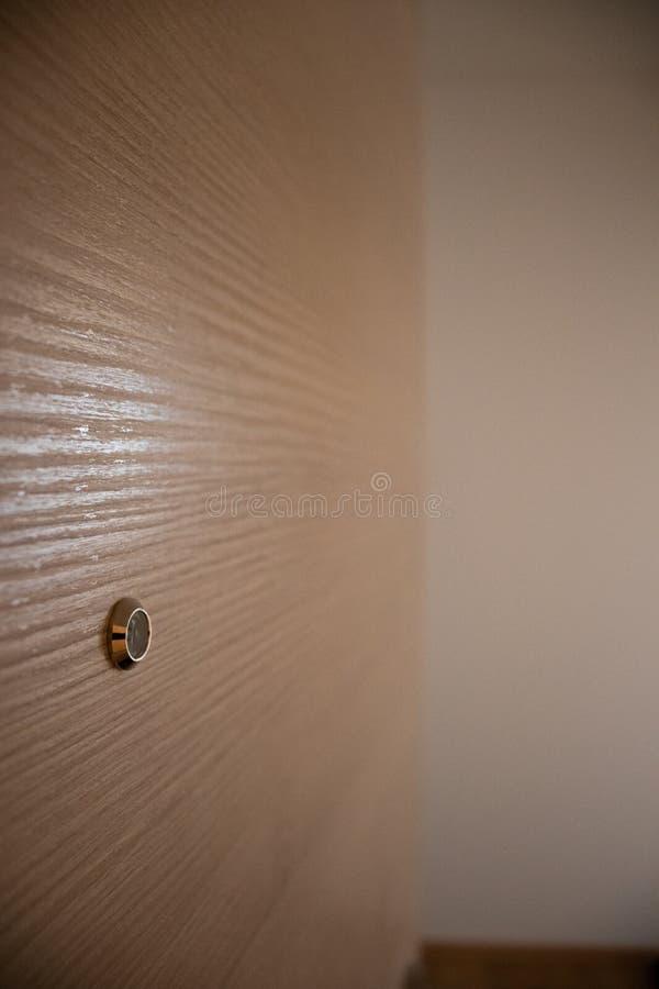 Zamyka w g?r? drzwiowego obiektywu peephole na brown drewnianej teksturze fotografia royalty free