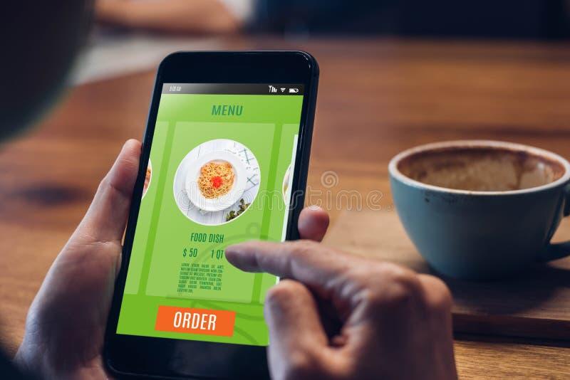 Zamyka w g?r? kobiety r?ki mienia karmowych onlinych mobilnych apps z gor?c? fili?ank? na sto?owym obsiadaniu przy sklep z kaw?,  fotografia stock