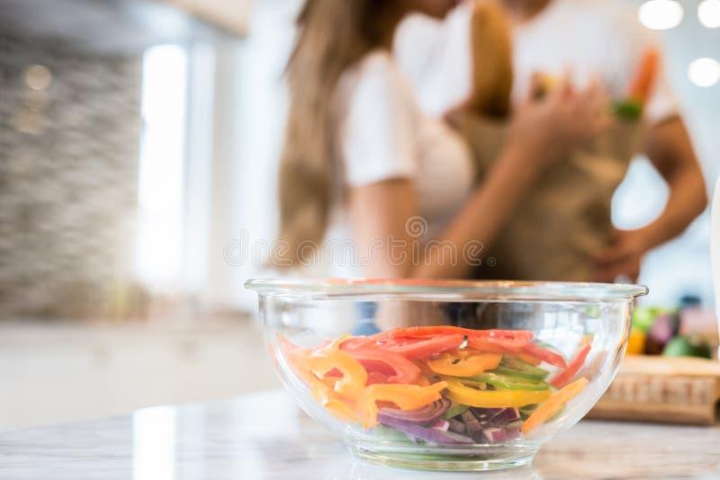 Zamyka w g?r? sa?atkowego pucharu na stole z rozmytym pary t?em w kuchni Pokrojony warzywa tomatoe w przejrzystym szklanym puchar zdjęcia royalty free