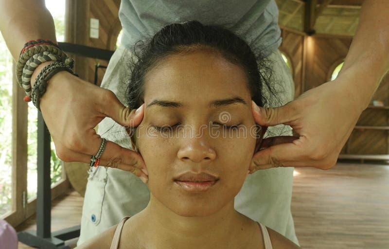 Zamyka w g?r? twarz portreta m?oda wspania?a i zrelaksowana Azjatycka Indonezyjska kobieta otrzymywa tradycyjnego twarzowego Tajl zdjęcia royalty free