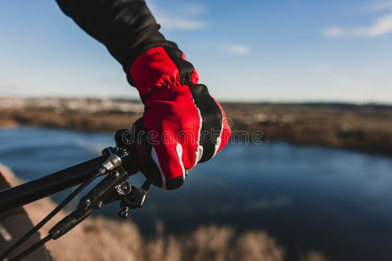 Zamyka w g?r? widoku cyklisty wyposa?enia handlebar i r?kawiczka M??czyzna Jedzie roweru puszka Skalistego wzg?rze przy zmierzche fotografia royalty free
