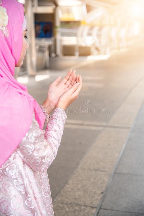 """ZamykajÄ… w górÄ™ mÅ'odego azjatykciego muzuÅ'maÅ""""skiego kobiety modlenia dla Allah, Arabskie modlitewne żeÅ""""skie dźwiganie rÄ zdjęcia royalty free"""