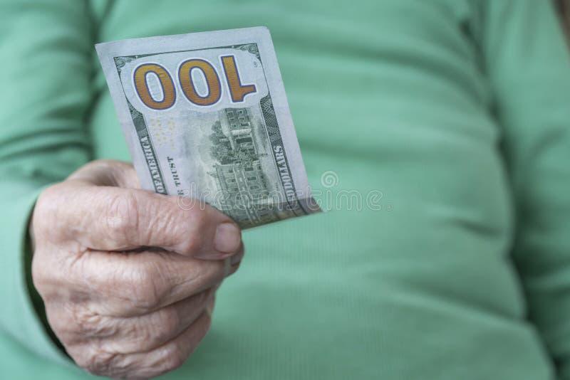 Zamykająca pomarszczona dłoń z banknotem stu amerykańskich dolarów obraz royalty free