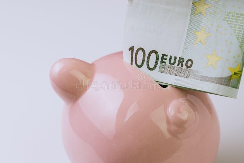 Zamykający up sto euro banknotów stawiających na górze różowych prosiątko półdupków fotografia stock