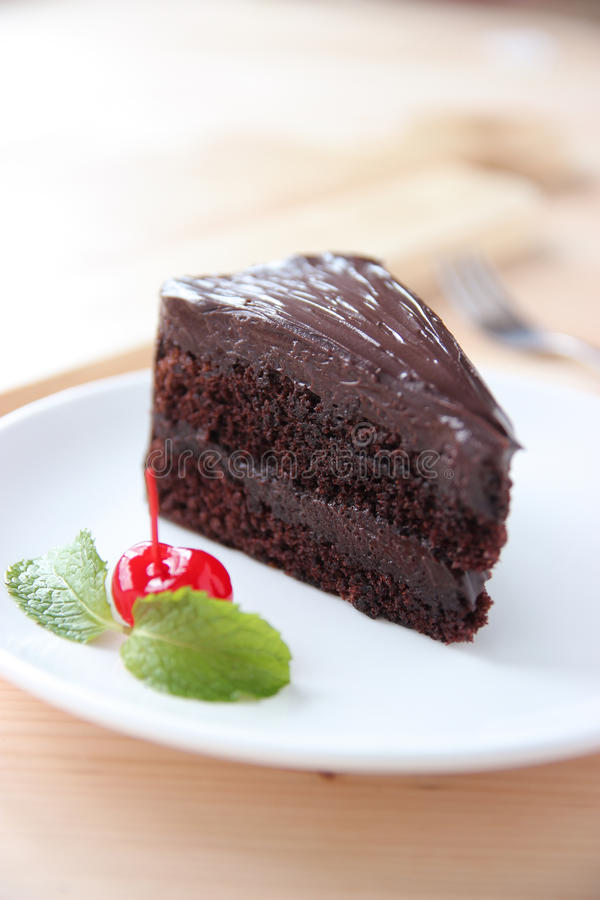 Zamykający w górę ciemnego czekoladowego torta z wiśnią i zielonymi nowymi liśćmi obraz royalty free