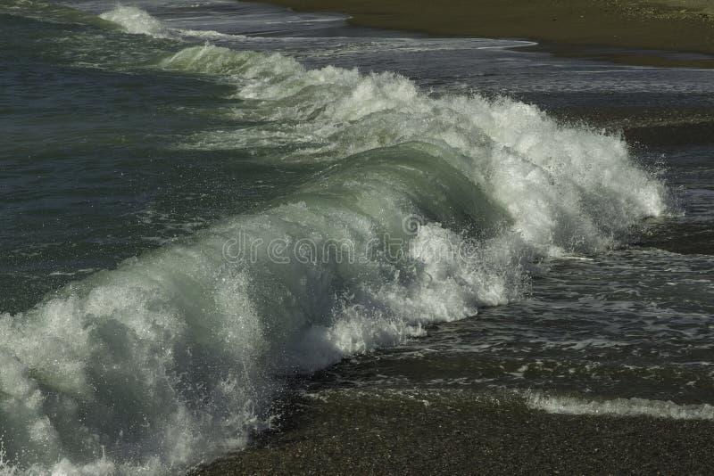 Zamykający w górę majestatycznego urquoise i jaskrawy - zieleń wskazujący pęcznienie rozbija w zmrok pebbled plażę na niebieskie  zdjęcie stock
