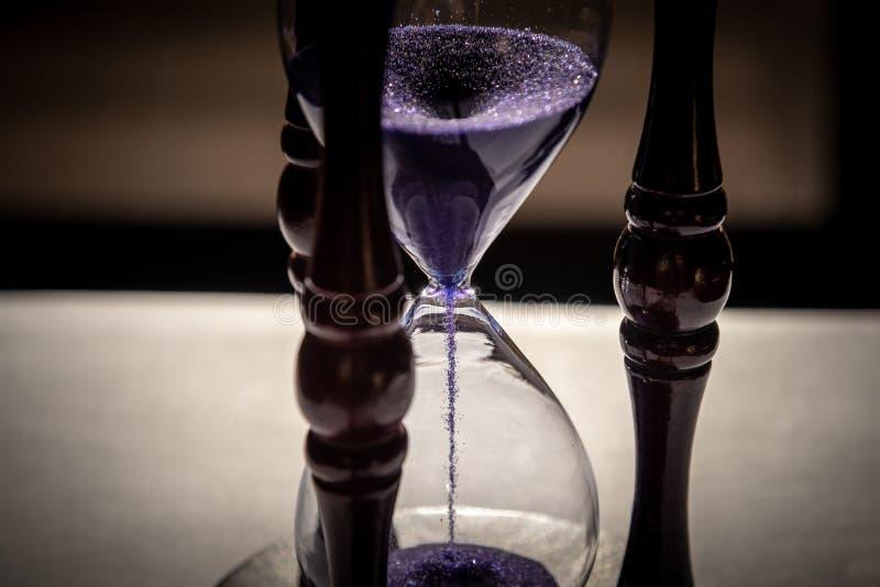 Zamykający w górę sandglass lub hourglass z fiołkiem, purpurowy piasek obraz stock