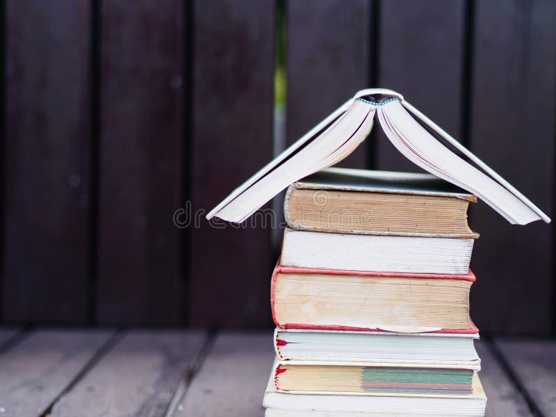 Zamykający w górę sterty książki z drewnianym tłem obrazy royalty free