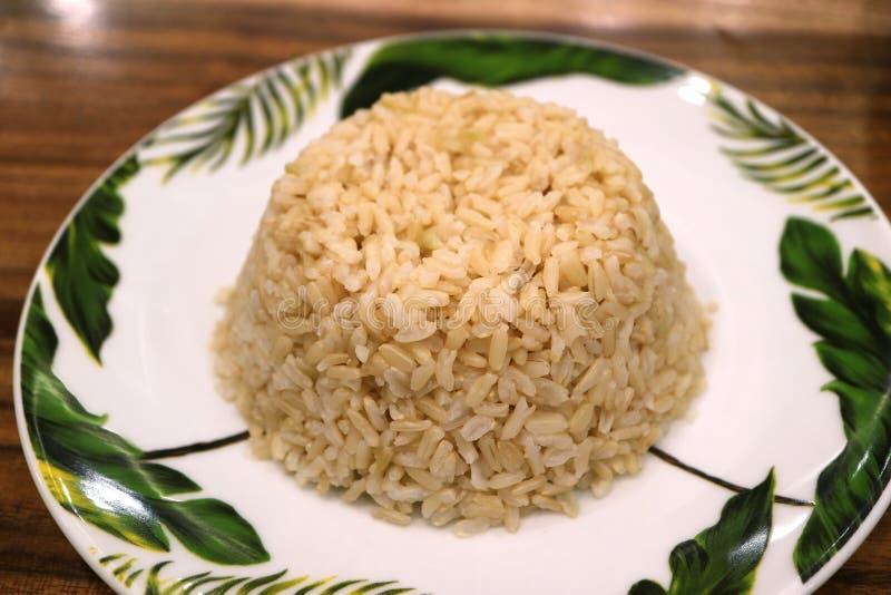 Zamykam płytę z ryżem brunatnym, serwowanym na drewnianym stole obrazy stock