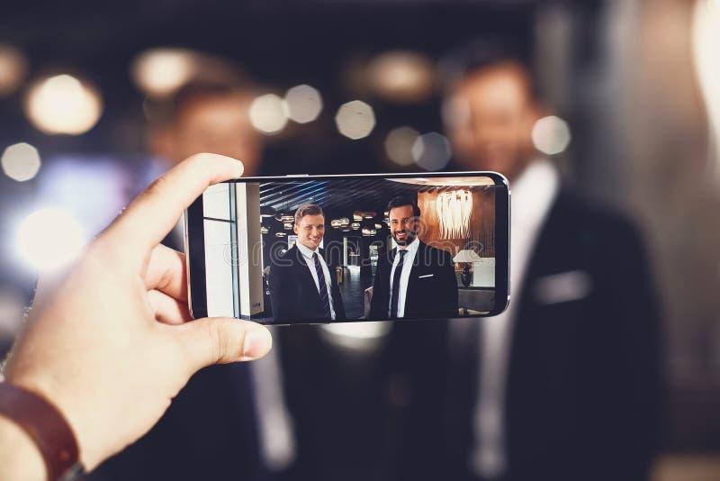Zamykanie nowoczesnego urzÄ…dzenia dziÄ™ki uÅ›miechniÄ™tym znajomym na ekranie fotografia stock