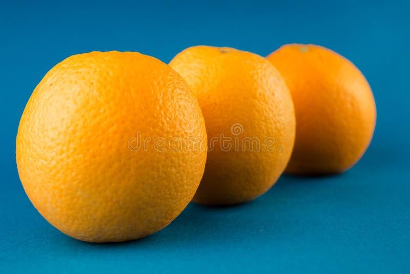 Zamykanie poziomego rzędu trzech pomarańczy pomarańczowych na jasnoniebieskim tle zdjęcie stock