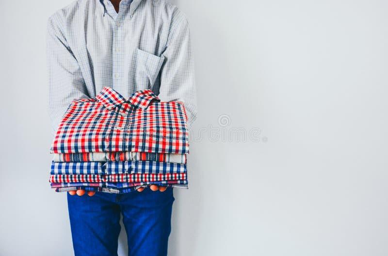Zamykanie stosu złożonej, kolorowej bluzy w dłoniach, człowiek trzymający złożone ubrania na białym tle, przestrzeń na kopię obraz royalty free