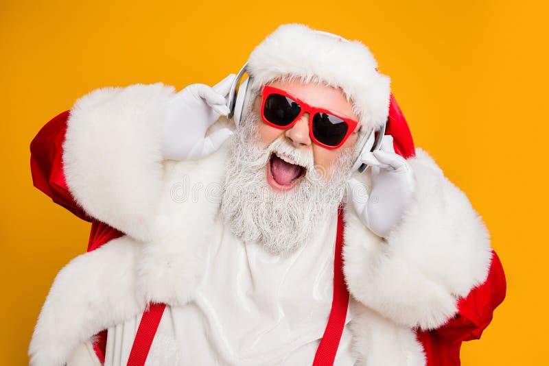 Zamykanie zdjęcia szalonych śmiesznych Świętych Mikołaja słucha muzyki na nowoczesnym słuchawce świętującej świąteczny wieczór no fotografia royalty free