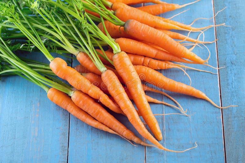 Zanahoria fresca y dulce en una tabla de madera gris foto de archivo