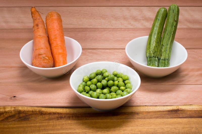 Zanahorias, calabacín y guisantes verdes imagenes de archivo