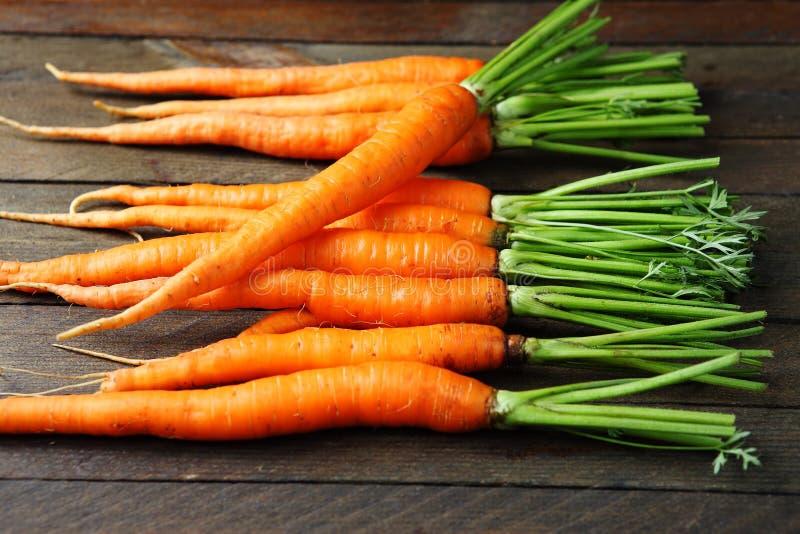 Zanahorias con los tops en la tabla fotografía de archivo libre de regalías