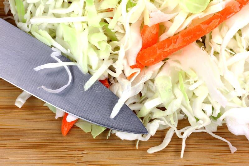 Zanahorias de la ensalada de col que cortan el cuchillo en tabla de cortar imagen de archivo