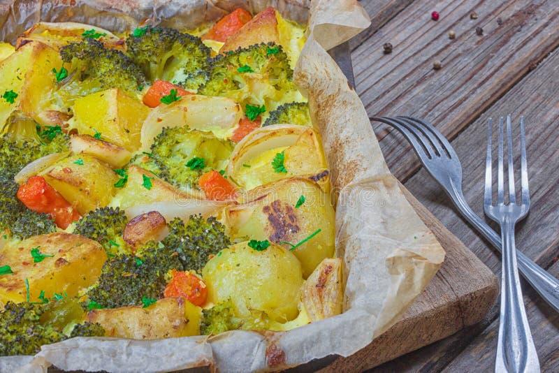 Zanahorias del bróculi, patatas, cebolla blanca y ajo con la cazuela del huevo del Cheddar en plato que cuece en fondo de madera  fotos de archivo libres de regalías