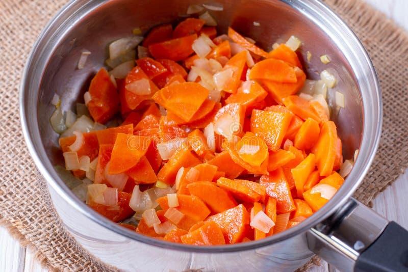 zanahorias estofadas con cebollas en una sartén metálica sobre la mesa foto de archivo