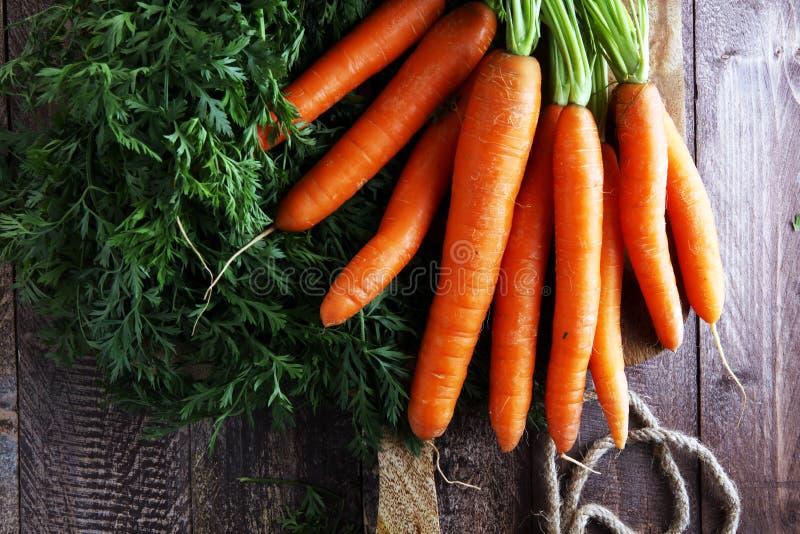 Zanahorias orgánicas frescas con las hojas verdes en fondo de madera VE imagen de archivo libre de regalías