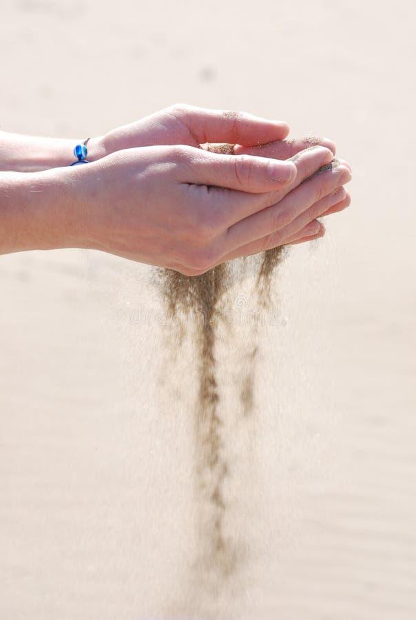 Zand dat handen doorneemt royalty-vrije stock foto