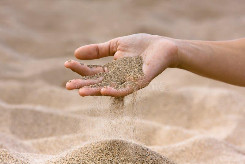 Zand die hand op de strandachtergrond doornemen stock fotografie