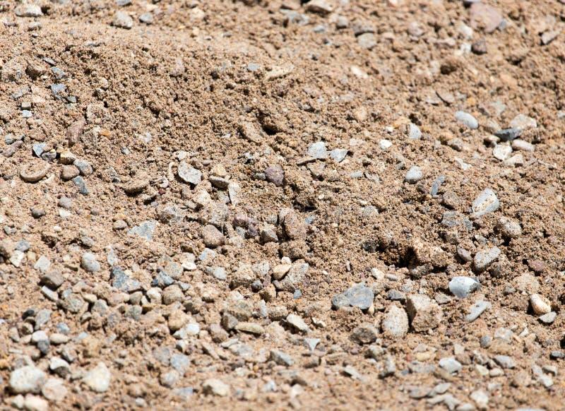 Zand met grint als achtergrond stock afbeelding
