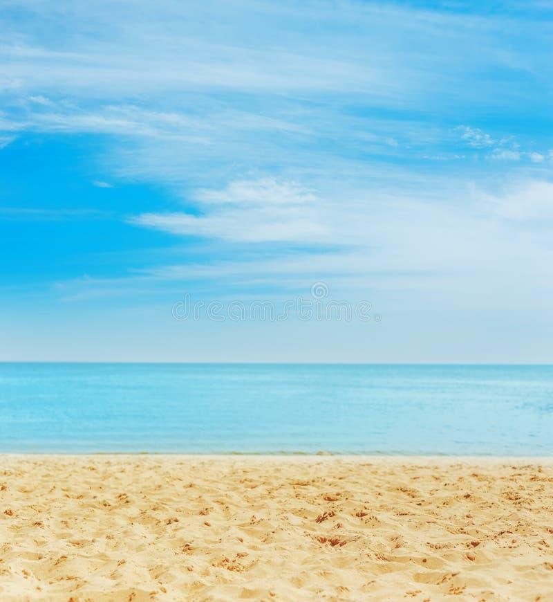 Zand op het strand overzees op horizon en blauwe hemel met wolken royalty-vrije stock afbeelding