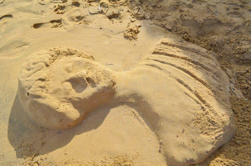 Zandbeeldhouwwerk in de vorm van een antiek standbeeld op het strand royalty-vrije stock afbeelding