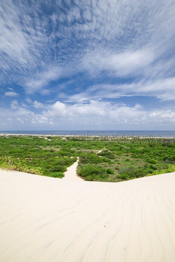 Zandduin die tot een weg door een groen gebied en het overzees leiden Bewolkte hemel stock afbeelding