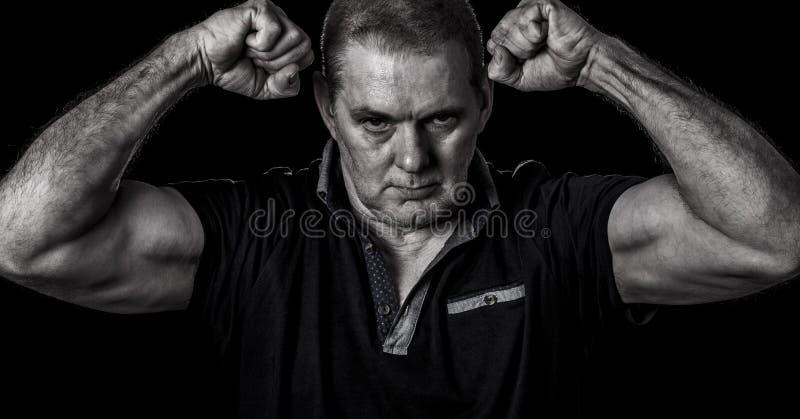 Zanderig beeld van het ongeschoren kerel stellen met dichtgeklemde gebogen vuisten en zijn bicepsen stock afbeelding
