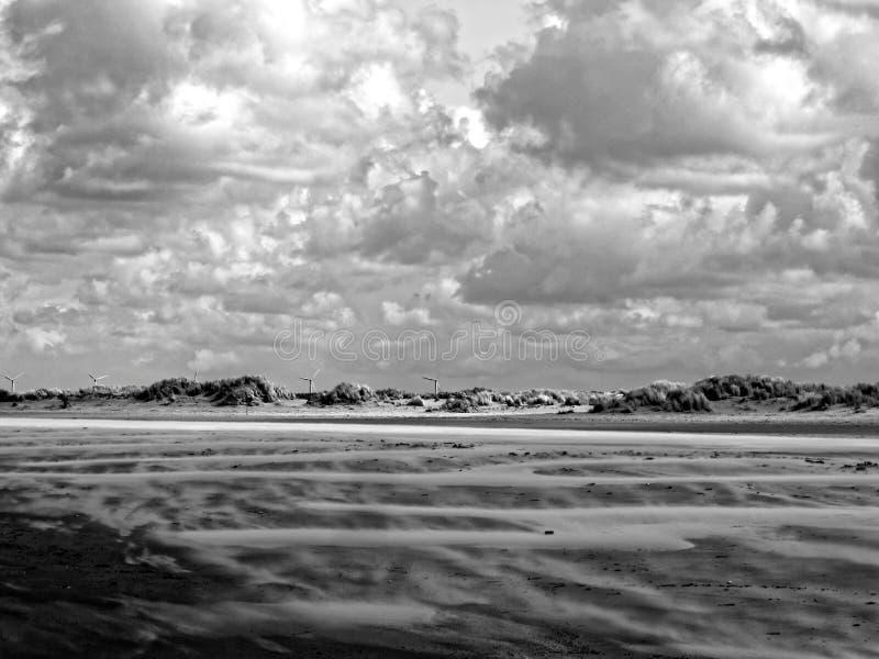 Zandgolven bij duinlandschap door dramatische hemel royalty-vrije stock afbeeldingen