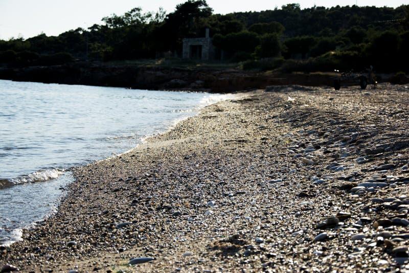 Zandig en pebbled strand in de zonsondergang royalty-vrije stock foto