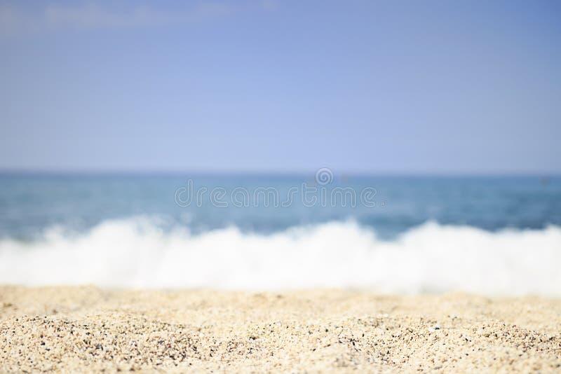 Zandig overzees strand op duidelijke de zomerdag Selectieve nadruk Zachte golven van blauwe overzees op tropisch strand met wit z royalty-vrije stock foto