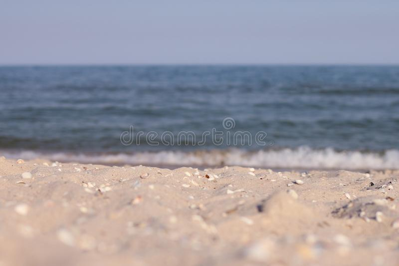 Zandig strand door het overzees tegen een blauwe hemel stock foto
