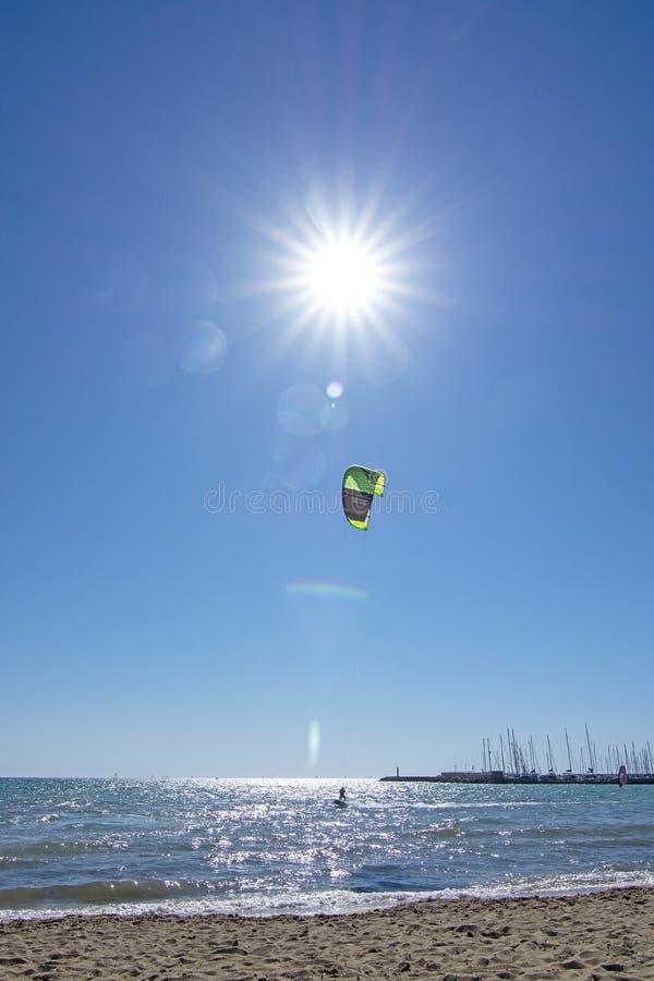 Zandig strand en kitesurfer het vliegen hoog tegen blauwe hemel met ster gevormde zon en gloed stock afbeeldingen