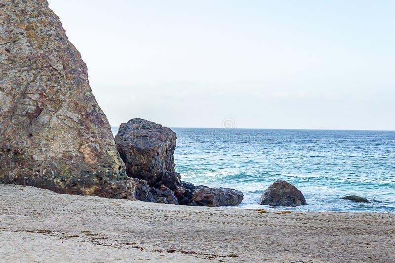Zandig strand en zwellende die oceaan door rotsachtige klippengezicht en keien wordt verdeeld stock afbeelding